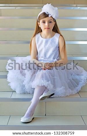 Nice little girl wearing white dress sitting on the steps