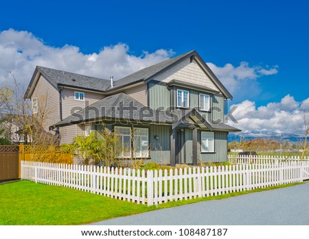 Nice looking house surrounded with the white country style wooden fence