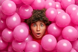 Nice looking surprised dark skinned woman stares with great surprisement at camera sticks out head through inflated pink balloons shocked how many guests came on party. Amazed ethnic birthday girl