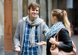 Nice-looking  young american male student chasing pleased girl on outdoor date. focus on boy