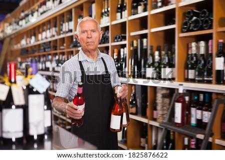 Nice male vintner working in modern wine shop, arranging wine bottles on racks. Foto d'archivio ©
