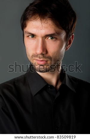 nice man in a black shirt with the beard poses funny faces