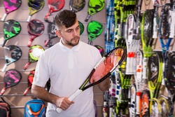 Nice man looking for modern tennis racket in store of sports equipment