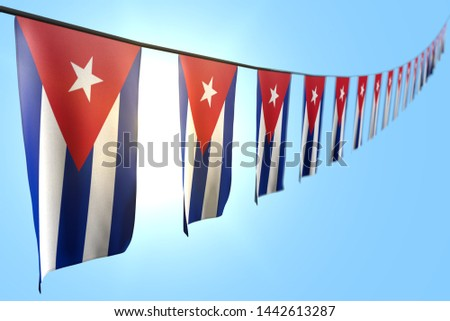 nice many Cuba flags or banners hangs diagonal on string on blue sky background with selective focus - any occasion flag 3d illustration
