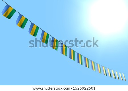 nice many Gabon flags or banners hangs diagonal on rope on blue sky background with soft focus - any celebration flag 3d illustration