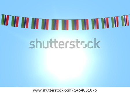 nice many Gambia flags or banners hangs on string on blue sky background - any holiday flag 3d illustration