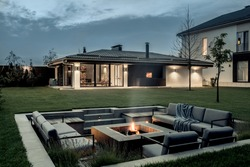 Nice modern estate with a two storey house, spa building, green lawn with trees and a relax zone with a burning fire pit on the background of the cloudy sky. Lamps are luminous. Horizontal.