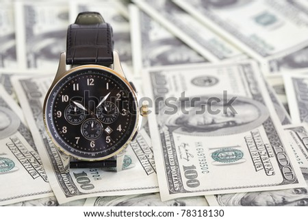 Nice modern wristwatch standing on background made from one hundred dollar notes