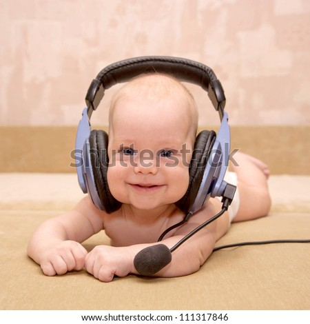 """Nice newborn baby with blue eyes smiling wearing a headset. """"Can I help you?"""" Or teaching a foreign language, or listening to a fairy tale."""
