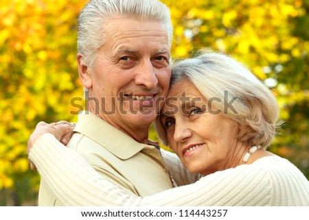 nice old couple posing at autumn park