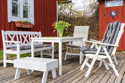 Nice outdoor sitting area in the garden. Amazing terrace in the garden. Toilet on the background. White outdoor furniture - table, chairs, bench. Tulips in the vase on the table. Estonia, Polva county