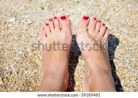 nice pedicure with red nail in the sand on the beach