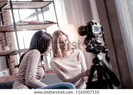 Nice pictures. Joyful blond woman smiling while showing photos to her friend