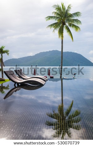 Nice pool with sun deck outdoors on bright summer day and coconut tree on the beach  #530070739