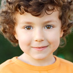 Nice portrait of a little boy with curly hair and brown eyes smiling