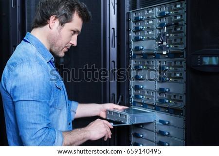 Nice professional technician installing the blade server #659140495