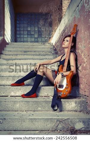Nice punk/rock player posing on street city location for stylish musician portraits