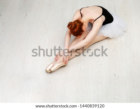 """Nice redheaded ballerina sit in """"dying swan"""" pose on the white wood floor She wears a light dance wear and a peach tutu. Top view photo. Horizontal. Copy space"""