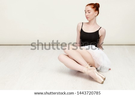 Nice redheaded ballerina sits on the white wood floor She wears a light dance wear and a peach tutu. Copy space #1443720785