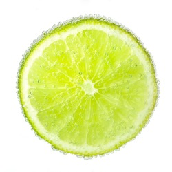 Nice ripe and juicy slice of a lime covered with bubbles in soda water.