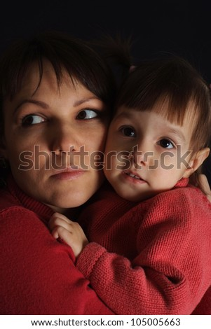 Nice sad Caucasian woman with a daughter on a dark background