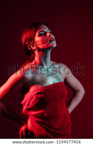 Nice shape of female body covered with red towel, against black background. Hot babe. Erotic concept. Erotica. Passionate concept. Passion. Adult . Sensual. Sensuality. Sensual #1194577456