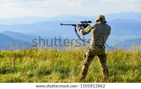 Nice shot. Army forces. Hunter hold rifle. Hunter mountains landscape background. Focus and concentration experienced hunter. Man military clothes with weapon. Brutal warrior. Rifle for hunting.