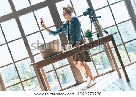 Stock Photo Nice shot. Full length of young woman taking selfie and smiling while standing near the window