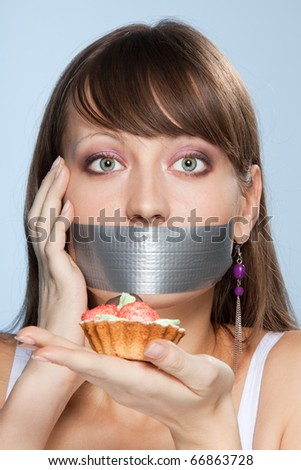 Nice smart girl do her best no to eat cake with worry in her eyes and sticky tape on her mouth