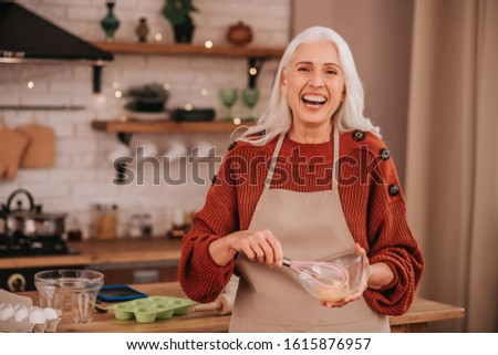 Nice smile. Grey-haired smiling lady smiling bright whipping milk in a bowl