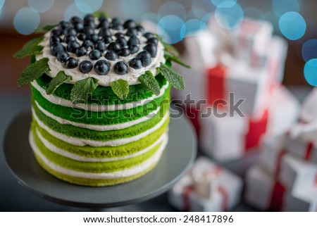 Nice sponge happy birthday cake with mascarpone and grapes with on the cake stand with gift boxes on festive light bokeh background
