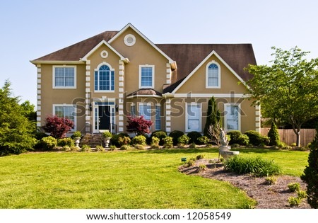 Nice suburban home with pretty landscaping - stock photo
