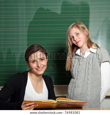 Nice teacher with a textbook and a student at the blackboard. They both smile at the camera