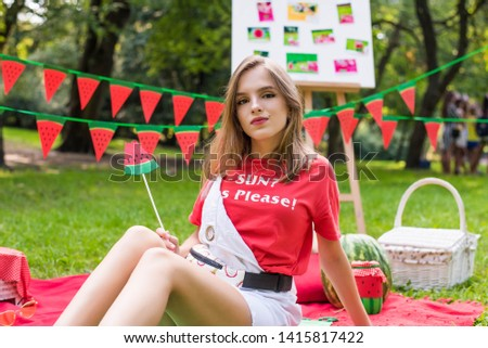 Nice teen girl having fun watermelon party In the park. Excellent sunny weather. Summer concept. Watermelon party, picnic, day. Nice teen girl having fun watermelon party In park yellow sunglasses