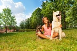 Nice teenage girl with her dogs in the park lawn