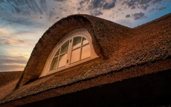 Nice thatched roof and vindow in sunset with a beautiful sky
