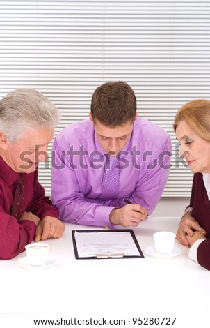 nice three business people sitting at office