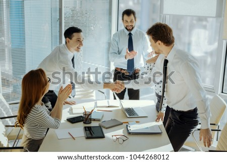 Nice to meet you. Charming upbeat young boss standing at the head of the table and introducing the participants of a business meeting to each other while they giving handshakes