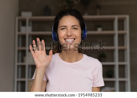 Nice to meet you. Portrait of happy smiling millennial latina female in headset look forward speak to camera wave hand. Young woman teacher tutor greet students begin remote class by webcam conference