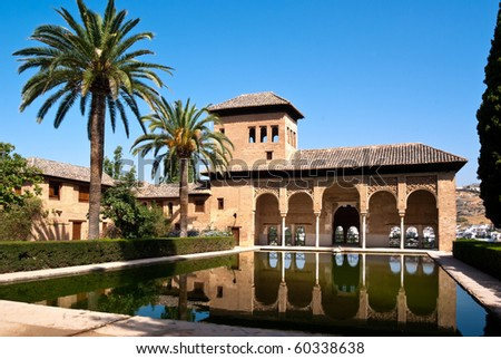 Nice view across a small pool and garden in the famous Alhambra in Granada/Spain.