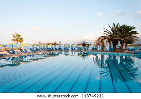 Nice view of the swimming pool with palm trees on the shore of the Mediterranean Sea in Greece. Crete.
