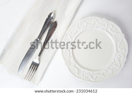 Nice vintage ceramic plate with silver fork and knife on wooden table