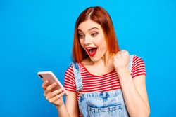 Nice vivid girlish red straight-haired happy smiling girl reading sms notification about winning, isolated over blue background, copy space