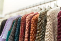 Nice warm colorful sweaters hang on hangers inside of a shopping mall. Beautiful clothes for winter autumn season. Fashion industry for women and men. Wool things for fall. Merchandise in a shop.
