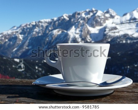 Nice warm cup of cappuccino of the snowy mountain