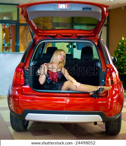 nice white girl sitting in luggage carrier of new red car in office