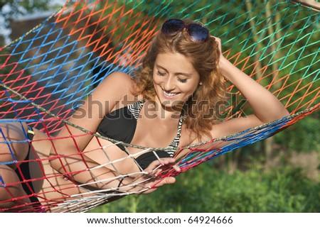 Nice woman wearing panama and lounging in hammock