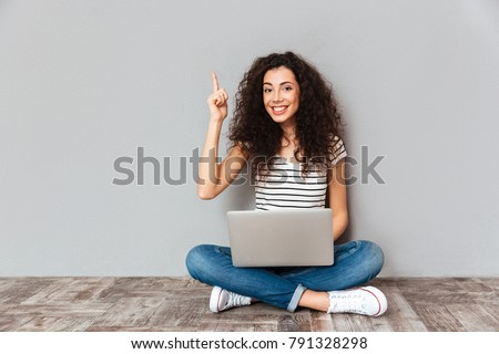 Nice woman with beautiful smile being excited to find useful information in internet via silver computer, gesturing eureka sitting in lotus pose on the floor