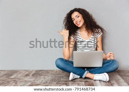 Nice woman with beautiful smile sitting in lotus pose on the floor with silver computer on legs gesturing thumb aside, submitting something copy space