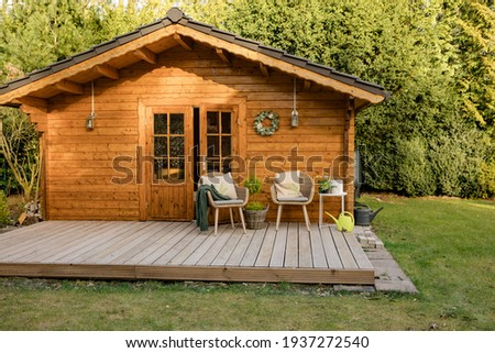 Nice wooden hut in a green garden. Garden shed with chairs and flowers. Spring mood. Drinking tea outside in spring.